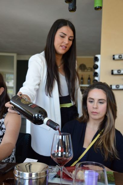 Veronica pouring a glass of Piccoli's wine during the tasting